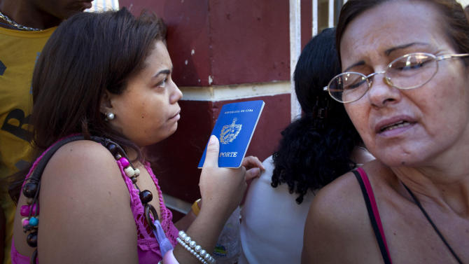 A woman holding her Cuban passport lines up with others at a migration office in Havana, Cuba, Monday, Jan. 14, 2013. Cubans formed long lines outside travel agencies and migration offices, as a highly anticipated new law took effect Monday, ending the island's much-hated exit visa requirement. The measure means the end of both real and symbolic obstacles to travel by islanders, though it is not expected to result in a mass exodus. Most Cubans are now eligible to leave with just a current passport and national identity card, just like residents of other countries. (AP Photo/Ramon Espinosa)