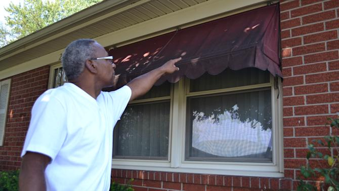 Chester Holloway points to a black, sooty substance on the awning in front of his Louisville, Ky. home on Wednesday, Sept. 12, 2012. Holloway lives across the street from a bourbon warehouse that city officials say must control the vapors coming from its bourbon barrels. They say the vapors promote the growth of the black fungus.  (AP Photo/Dylan Lovan)
