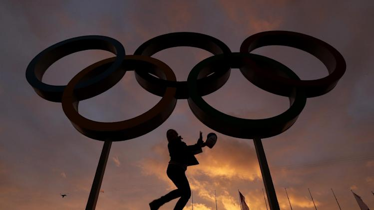 AP10thingsToSee - A woman poses for a photo with the Olympic rings in Olympic Park as preparations continue for the 2014 Winter Olympics in Sochi, Russia on Wednesday, Feb. 5, 2014
