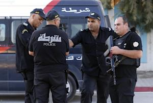 Tunisian police officers guard the street near the…
