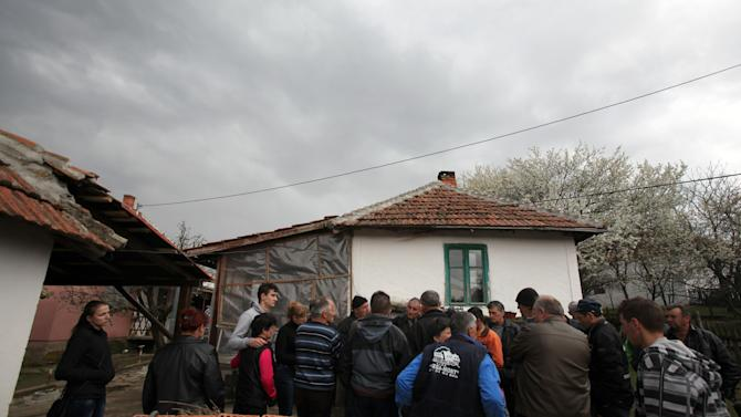 Locals gathered in front of the house of the Despotovic family whose five members, including a two-year-old, were killed in the shooting spree in the village of Velika Ivanca, Serbia, Tuesday, April 9, 2013. A 60-year-old man gunned down 13 people, including a baby, in a house-to-house rampage in a quiet village on Tuesday before trying to kill himself and his wife, police and hospital officials said. Belgrade emergency hospital spokeswoman Nada Macura said the man, identified as Ljubisa Bogdanovic, used a handgun in the shooting spree at five houses. The dead included six women. (AP Photo/Darko Vojinovic)