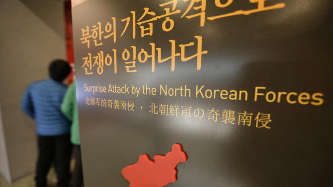 Visitors stand near the sign written in Korean, English, Chinese and Japanese for an exhibition of the Korean War area at the Korea War Memorial Museum in Seoul, South Korea, Tuesday, Jan. 29, 2013. North Korea appears all set to detonate an atomic device, but confirming the explosion when it takes place will be virtually impossible for outsiders, specialists said Tuesday. (AP Photo/Lee Jin-man)