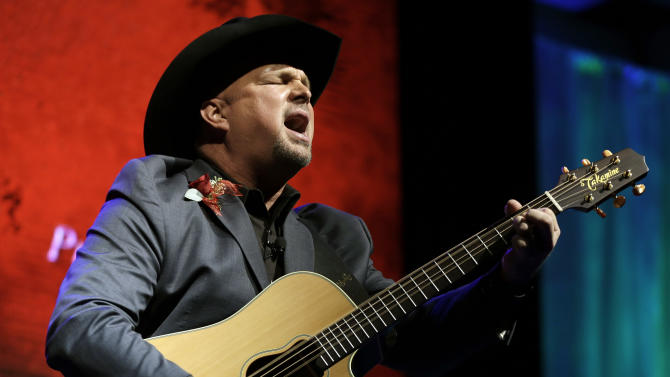 """Garth Brooks sings """"Papa Loved Mama,"""" a song written by Kim Williams, as Williams is inducted into the Nashville Songwriters Hall of Fame on Sunday, Oct. 7, 2012, in Nashville, Tenn. (AP Photo/Mark Humphrey)"""