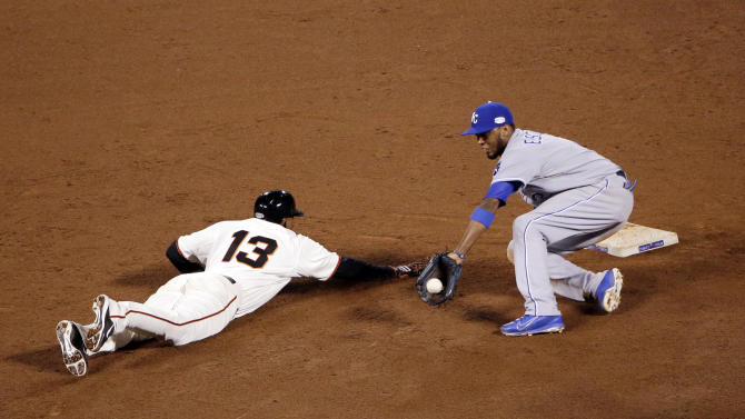 San Francisco Giants' Joaquin Arias is safe at second on a throw by Kansas City Royals' catcher Salvador Perez to Alcides Escobar, right, during the sixth inning of Game 4 of baseball's World Series Saturday, Oct. 25, 2014, in San Francisco. (AP Photo/Marcio Jose Sanchez)