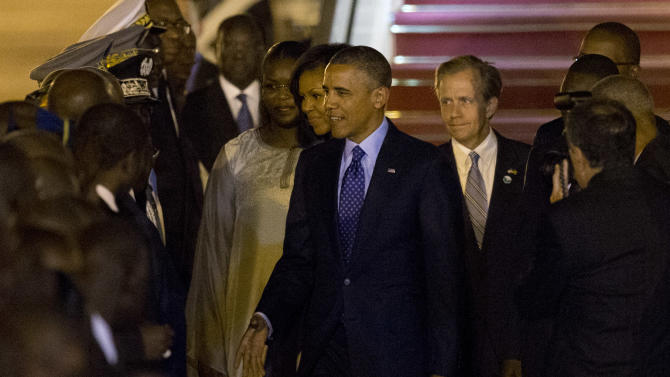 U.S. President Barack Obama, center, accompanied by first lady Michelle Obama, center left, greets Senegalese dignitaries as he arrives at the airport in Dakar, Senegal, Wednesday, June 26, 2013. President Obama opened a weeklong trip to Africa on Wednesday, a three-country visit aimed at overcoming disappointment on the continent over the first black U.S. president's lack of personal engagement during his first term. (AP Photo/Rebecca Blackwell)