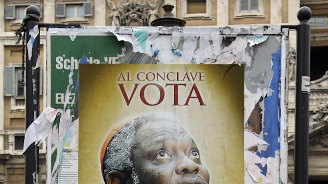 """FILE - This March 1, 2013 file photo shows a poster with a picture of Nigerian Cardinal Peter Kodwo Appiah Turkson with writing reading: """"For the next conclave vote for Turkson"""", in front of the St. Mary Major Basilica in Rome. These are crazy days in Rome - where limbo reigns in parliament and papacy. Italy is usually a pretty anarchic place, with people bucking rules on everything from crossing the street to paying taxes. But the anarchy's going a bit far: Who's running the country? Who's running the church? Nobody really knows. (AP Photo/Gregorio Borgia, files)"""