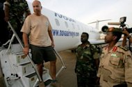One of four foreigners captured by Sudanese military in the Heglig oilfield area April 28, is escorted off an airplane in Khartoum. The British embassy was &quot;urgently&quot; investigating on Sunday the arrest in Sudan of one of its citizens, who was among four foreigners the Sudanese military said it captured in the tense Heglig oil region