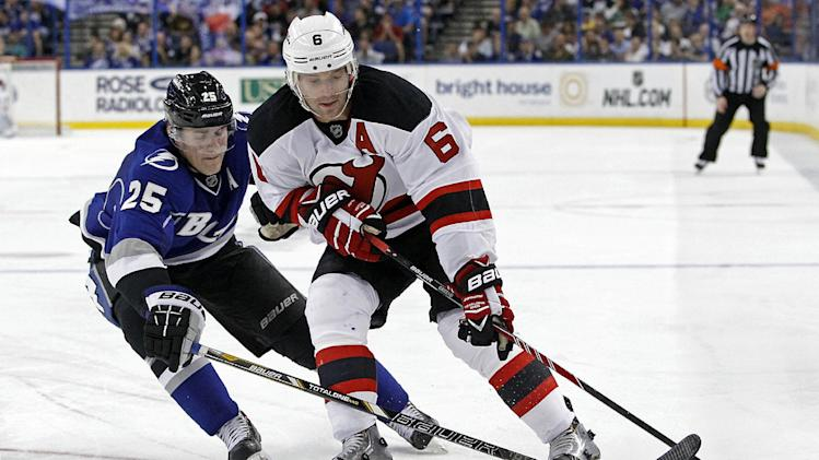 Tampa Bay Lightning defenseman Matthew Carle (25) and New Jersey Devils defenseman Andy Greene (6) reach for the puck during the third period of an NHL hockey game Saturday, March 15, 2014, in Tampa, Fla. The Lightning won 3-0. (AP Photo/Brian Blanco)
