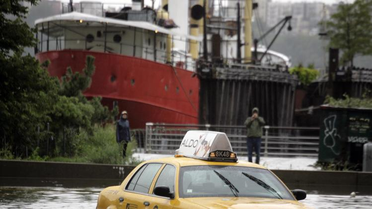 A New York City taxi is stranded in deep water on Manhattan's West Side as Tropical Storm Irene passes through the city, Sunday, Aug. 28, 2011 in New York. Although downgraded from a hurricane to a tropical storm, Irene's torrential rain couple with high winds and tides worked in concert to flood parts of the city. (AP Photo/Peter Morgan)