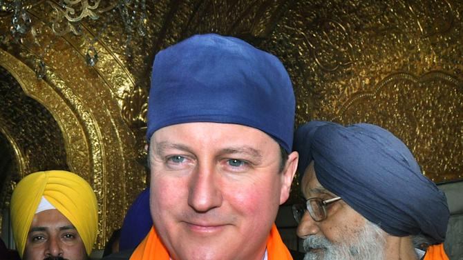 British Prime Minister David Cameron visits the Golden Temple, Sikh's holiest shrine in Amritsar, India, Wednesday, Feb. 20, 2013. Cameron also laid a mourning wreath at Jallianwala Bagh, the site of a notorious 1919 massacre of hundreds of Indians by British colonial forces. More than 300 Indians were killed during the massacre on unarmed Indians attending a rally, which galvanized the national independence movement. (AP Photo/Prabhjot Gill)