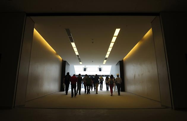 Officials and media proceed down the players' entrance to the pitch during a tour of the Arena Sao Paulo stadium in Sao Paul
