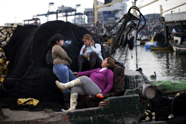 "FILE - In this Dec. 6, 2012 file photo, Cyntia de la Cruz sits on a sofa with her colleagues Kimberly, right, and Wendy as they take a smoke break after unloading crates of fish from ""boliches,"" the P"