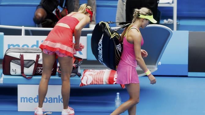 Bouchard of Canada walks past Sharapova of Russia after losing her women's singles quarter-final match at the Australian Open 2015 tennis tournament in Melbourne