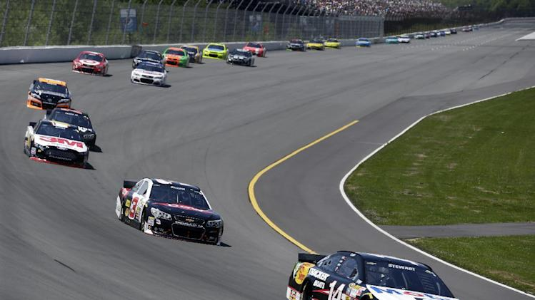 Driver Tony Stewart (14) leads a pack of race cars during the NASCAR Sprint Cup series Pocono 400 auto race, Sunday, June 8, 2014, in Long Pond, Pa