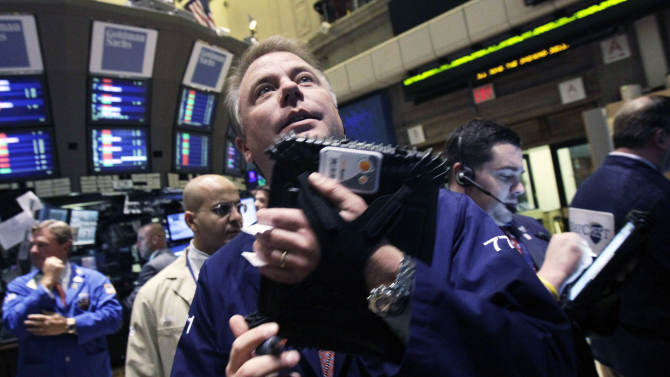 FILE - In this Tuesday, Oct. 9, 2012, file photo, trader F. Hill Creekmore works on the floor of the New York Stock Exchange. Stock futures are edging higher Friday, Oct. 12, 2012, after mixed third-quarter results from two major banks, which has been the pattern all week as the U.S. earnings season kicks off. (AP Photo/Richard Drew, File)
