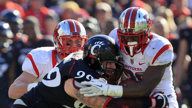 Rutgers running back Savon Huggins is tackled by Cincinnati defensive lineman Dan Giordano (99) after a short gain in the first half of an NCAA college football game, Saturday, Nov. 17, 2012, in Cincinnati. (AP Photo/Al Behrman)