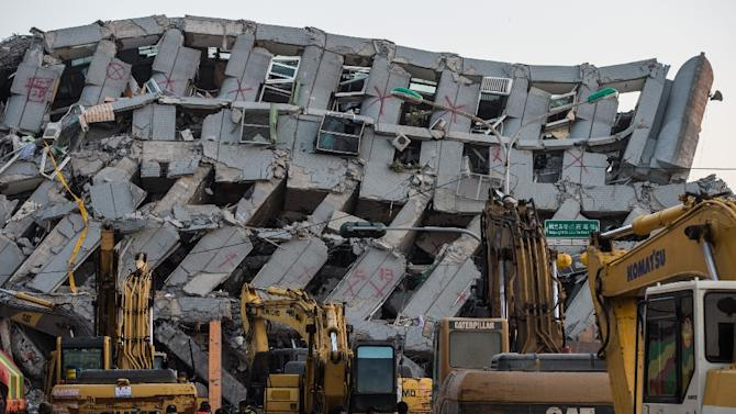 Excavator vehicles and rescue workers in front of the collapsed building in the southern Taiwanese city of Tainan
