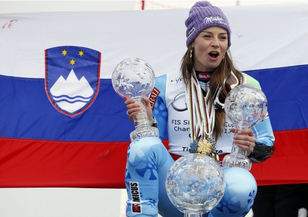 Slovenia's Maze poses with her women's overall, Giant Slalom and Super-G World Cup trophies at the Alpine Skiing World Cup finals in Lenzerheide