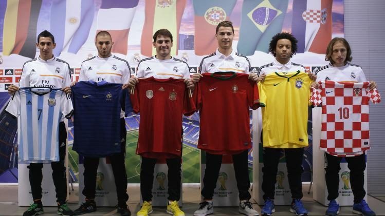 Real Madrid's players pose with jerseys during a news conference to discuss the draw for the 2014 World Cup at the Valdebebas training grounds, outside Madrid