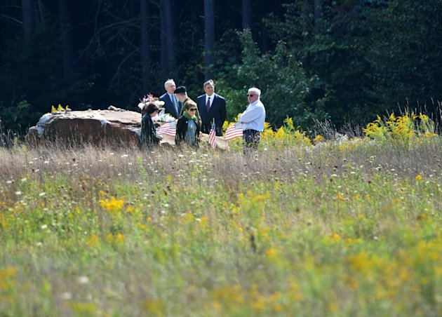 Defense Secretary Leon Panetta, center, Patrick White, a representative of victim's families, second from left, and others, visit the crash site at a day ahead of the 11th anniversary of the 9/11 atta