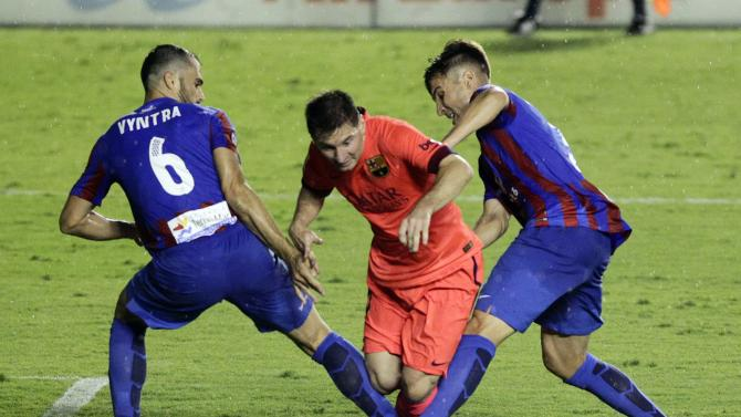 Barcelona's Lionel Messi fights for the ball with Levante's Loukas Vyntra and Tono Garcia during their Spanish first division soccer match at the Ciudad de Valencia stadium in Valencia