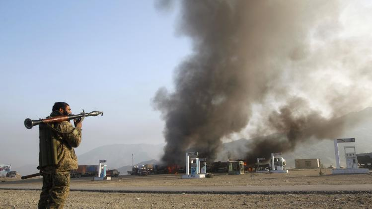 A member of the Afghan security forces watches burning NATO supply trucks after what police officials say was an attack by militants in the Torkham area
