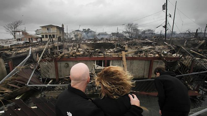FILE - In this Tuesday, Oct. 30, 2012 file photo, Robert Connolly, left, embraces his wife, Laura, as their son Kyle leans over, at right, as they survey the remains of the home owned by Laura's parents that burned to the ground in the Breezy Point section of New York, following Superstorm Sandy. Sandy ran up a $42 billion bill on New York and the state and New York City are making big requests for disaster aid from the federal government, according to one of Gov. Andrew Cuomo's administration officials. (AP Photo/Mark Lennihan, File)