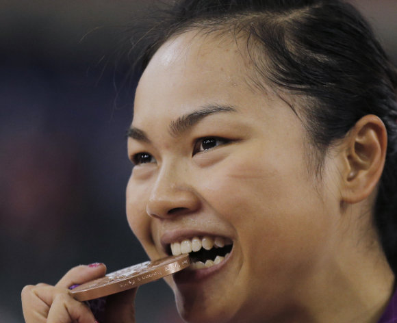 Wai Sze Lee of Hong Kong bites the bronze medal after the track cycling women's keirin event, during the 2012 Summer Olympics in London, Friday, Aug. 3, 2012. (AP Photo/Christophe Ena)