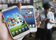 Samsung Electronics' Galaxy S4 (L) and Apple's iPhone 5 are seen in this file picture illustration taken in Seoul on May 13, 2013. REUTERS/Kim Hong-Ji/Files