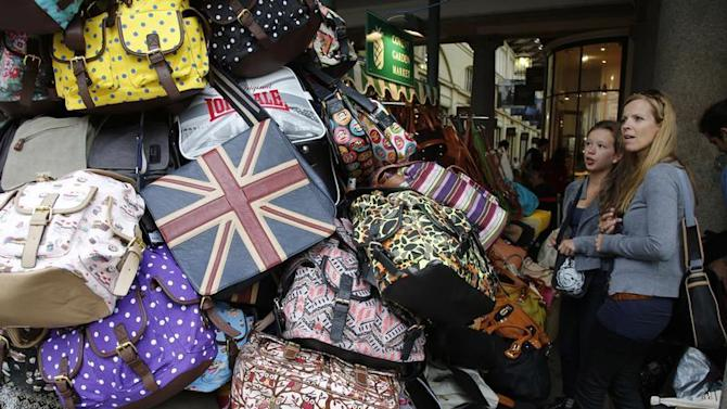 Shoppers browse handbags for sale at Covent Garden market in central London