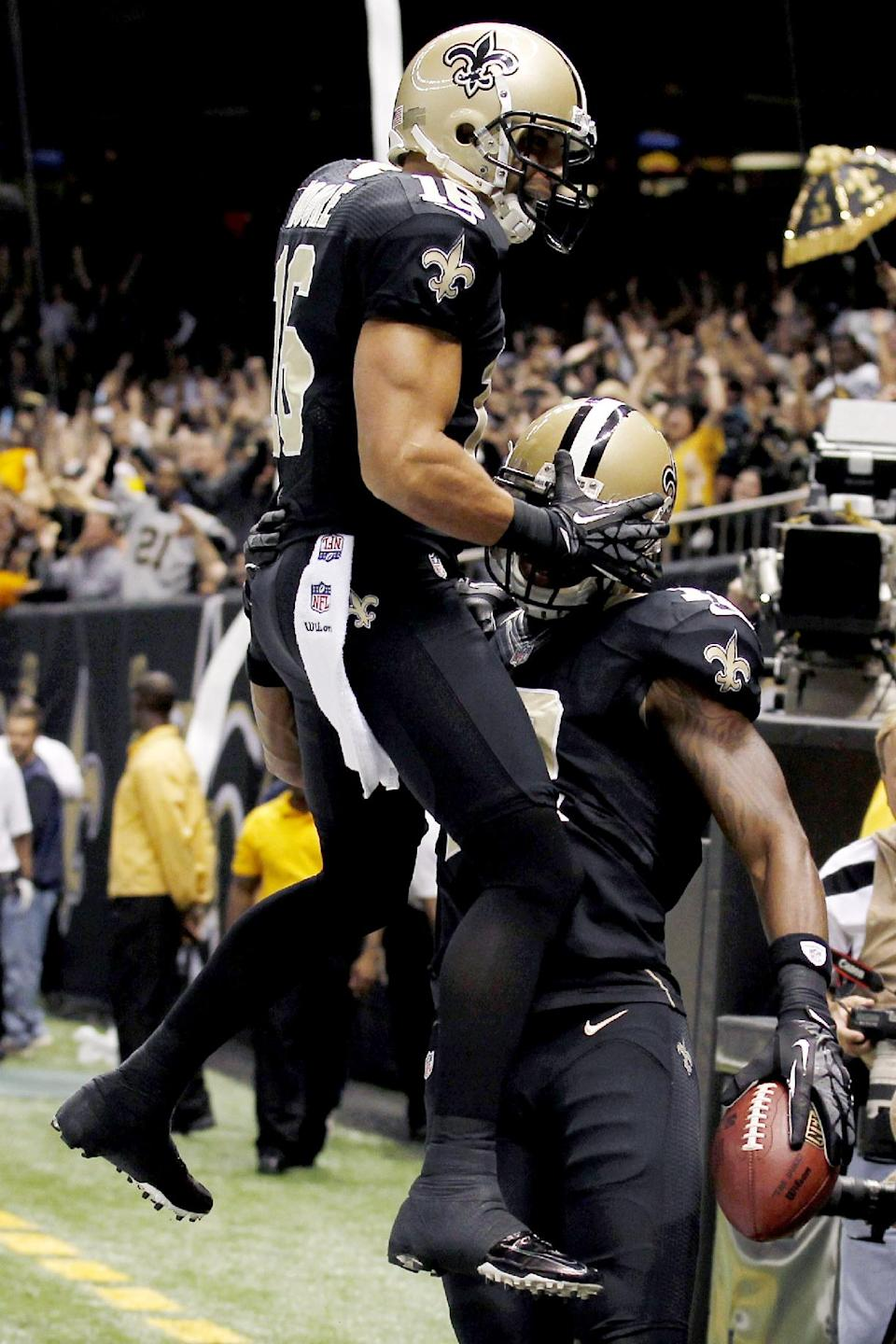 New Orleans Saints wide receiver Lance Moore (16) leaps on wide receiver Marques Colston after Colston's touchdown reception during the first half of an NFL football game against the Philadelphia Eagles at Mercedes-Benz Superdome in New Orleans, Monday, Nov. 5, 2012. (AP Photo/Bill Haber)