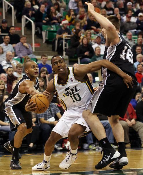 Utah Jazz's Alec Burks (10) drives the basket as San Antonio Spurs' guard Patty Mills, left, and San Antonio Spurs' Aron Baynes (16) defend in the second half of an NBA basketball game on