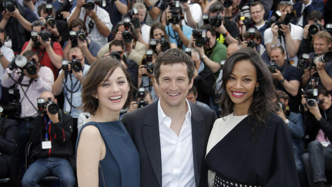 Actress Marion Cotillard, left, director Guillaume Canet, centre, and actress Zoe Saldana pose for photographers during a photo call for the film Blood Ties at the 66th international film festival, in Cannes, southern France, Monday, May 20, 2013. (AP Photo/Lionel Cironneau)