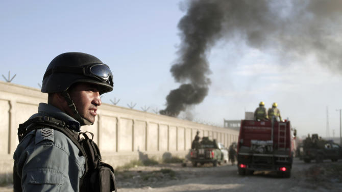 An Afghan security force member stands guard near the entrance gate of a NATO compound following a suicide bombing in Kabul, Afghanistan, Tuesday, July 2, 2013. Militants blew up a suicide car bomb at the gate to the NATO compound in Kabul early Tuesday and attacked guards with small-arms fire, killing four guards and two civilians, police said. All four suicide attackers were also killed. (AP Photo/Rahmat Gul)