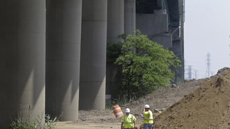 """In this June 3, 2014 photo, workers stand between the Interstate 495 bridge over the Christina River, left, and a dirt pile near Wilmington, Del., after the bridge was closed due to the discovery of four tilting support columns. Delaware Transportation Secretary Shailen Bhatt said engineers are looking at all geotechnical issues and have determined that the dirt pile, which appears to be partly in the transportation department's right of way, could be a factor. """"We don't know what the effect of that weight is"""" underground, he said. (AP Photo/Patrick Semansky)"""