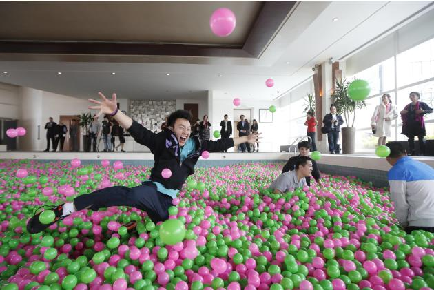 "A man jumps in a swimming pool filled with pink and green plastic balls during a Guinness World Records attempt of the Largest Ball Pit as part of the ""Pink October"" campaign at Kerry Hotel in Pudong,"