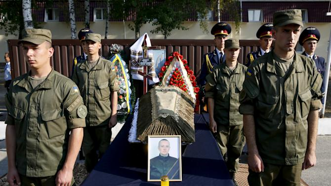 Members of Ukraine's National Guard stand near coffin with body of their comrade Ihor Debrin during memorial service outside Kiev