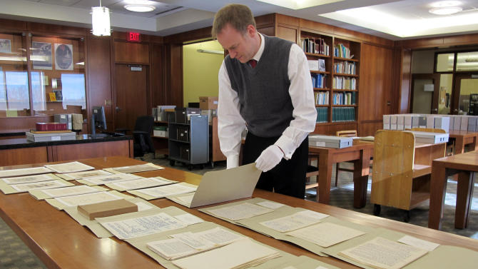 "In this Nov. 27, 2012 photo Marquette University Archivist Bill Fliss arranges some of the 11,000 J.R.R. Tolkien papers the university owns in the library of the Milwaukee school _ home to the largest Tolkien collection in the world. Marquette offered it's first class on J.R.R. Tolkien during the fall semester as part of their anniversary celebration of the 75th anniveresary of the ""The Hobbit"" being published. When ""The Hobbit"" movie opens Friday, the 32 students in the class will be nearly experts on J.R.R. Tolkien. (AP Photo/Carrie Antlfinger)"