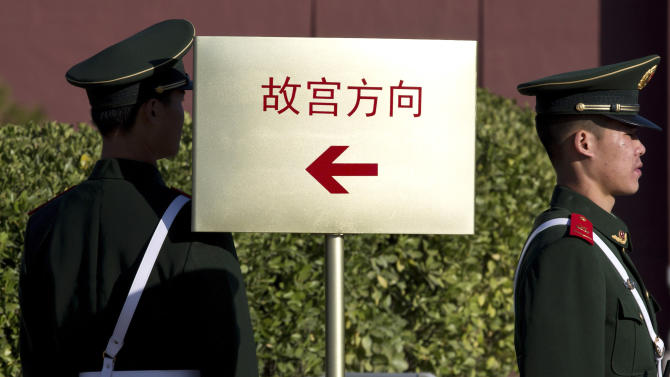 Chinese paramilitary policemen stand guard near a signboard showing direction to Forbidden City, in Beijing Thursday, Nov. 1, 2012. Beijing is tightening security as its all-important Communist Party congress approaches, and some of the measures seem bizarre. Most of the security measures were implemented in time for Thursday's opening of a meeting of the Central Committee. (AP Photo/Andy Wong)