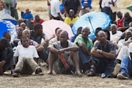 Striking Lonmin mine workers wait to hear how successful their wage negotiations have been. Worker turnout at the strike-hit South African mine plummeted