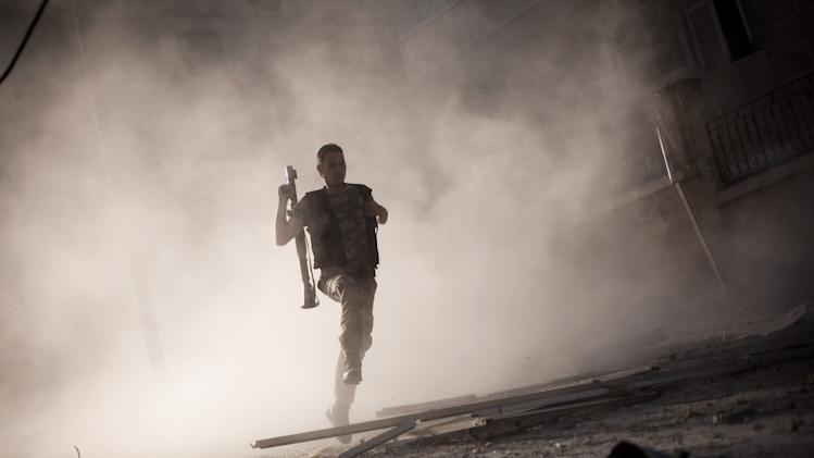 A Free Syrian Army fighter runs after attacking a tank with a rocket-propelled grenade during fighting in the Izaa district in Aleppo, Syria, Friday, Sept 7, 2012. (AP Photo/Manu Brabo, File)