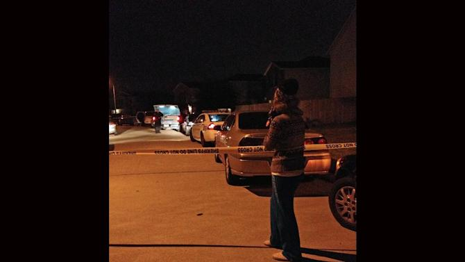 An unidentified parent waits on a child at the scene of a suburban Houston shooting early Sunday Nov. 10, 2013. Two people have been killed and at least 22 others hurt when gunfire rang out at the large house party in the Cypress-area of Houston, sending partygoers fleeing in panic, according to authorities. (AP Photo/Houston Chronicle, Anita Hassan)