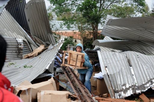 <p>A worker at a clothes factory destroyed by a storm tries to salvage whatever is left, in Mariano Alonso Roque, on September 19, 2012. Fierce storms packing 140-kilometer (87-mile) an hour winds tore across the heart of South America on Wednesday, killing five people in Paraguay, two in Uruguay and two in Bolivia.</p>