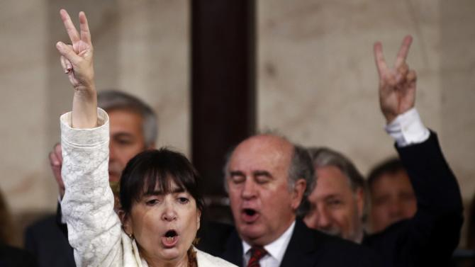 Sister of Argentina's President Cristina Fernandez de Kirchner gestures next to Secretary of Intelligence Parrilli as they sing the national anthem during the opening session of the 133rd legislative term of Congress in Buenos Aires