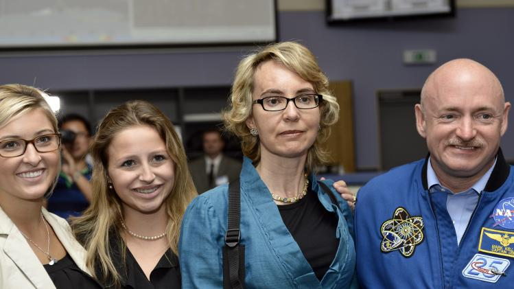 From left: Claudia and Claire, daughters of former U.S. Congresswoman Gabrielle Giffords, and  her husband Mark Kelly, right, NASA astronaut and commander of mission STS-134, pose for a picture at the Alpha Magnetic Spectrometer (AMS) Payload Operations and Command Center (POCC) at the European Organization for Nuclear Research (CERN) in Meyrin near Geneva, Switzerland, Wednesday, July 25, 2012.  Giffords toured the European particle physics laboratory Wednesday, cheerfully facing reporters while surrounded by family and aides but saying little during her first trip abroad since being shot in the head in January of last year. Two days after riding a cable car up into the French Alps, Giffords accompanied her husband, retired astronaut Mark Kelly, on a visit to the European Center for Nuclear Research, which assembled a  US$2 billion cosmic ray detector that Kelly and his team of astronauts carried to the International Space Station.  (AP Photo/Keystone/Martial Trezzini)