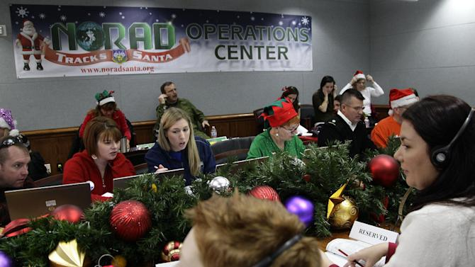 Volunteers take phone calls from children asking where Santa is and when he will deliver presents to their house, during the annual NORAD Tracks Santa Operation, at the North American Aerospace Defense Command, or NORAD, at Peterson Air Force Base, in Colorado Springs, Colo., Monday Dec. 24, 2012. Over a thousand volunteers at NORAD handle more than 100,000 thousand phone calls from children around the world every Christmas Eve, with NORAD continually projecting Santa's supposed progress delivering presents. (AP Photo/Brennan Linsley)