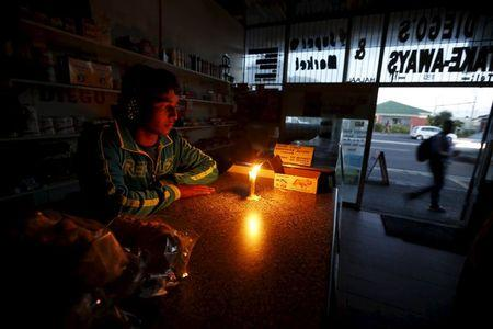 Shopkeeper waits for customers in his candlelit fast food store during a load shedding electricity blackout in Cape Town