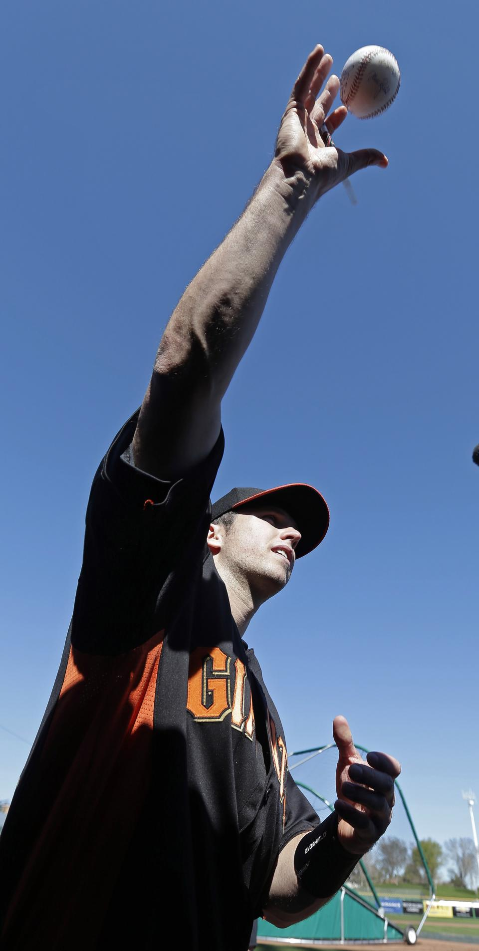 San Francisco Giants' Buster Posey tosses a baseball back to a fan after autographing it following a spring training baseball workout Wednesday, Feb. 13, 2013, in Scottsdale, Ariz. (AP Photo/Darron Cummings)