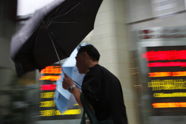 A man walks past a screen showing the stock price at a bank in Hong Kong Monday, July 23, 2012. Asian stock markets slid Monday as investors fretted about Europe's debt crisis and worries persisted over a slowdown in China. (AP Photo/Kin Cheung)