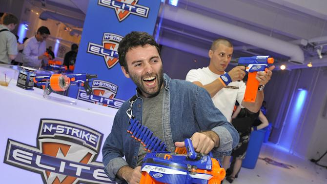 COMMERCIAL IMAGE -  Guests try out the new Nerf N-Strike Elite Hail-Fire blaster from Hasbro at the party celebrating the 9.9.12 Elite launch in New York, Thursday, June 21, 2012.  The N-Strike Elite blasters deliver unprecedented distance, shooting up to 75 feet. (Photo by Charles Sykes/Invision for Hasbro/AP Images)